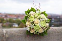 Το ελεφαντόδοντο και η πράσινη γαμήλια ανθοδέσμη των τριαντάφυλλων και του γαρίφαλου ανθίζουν στο υπόβαθρο πόλεων στοκ φωτογραφίες με δικαίωμα ελεύθερης χρήσης