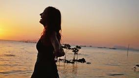 Το ελεύθερο ευτυχές τρέξιμο γυναικών στα περιστρεφόμενα όπλα παραλιών η απόλαυση της φύσης που χορεύει θαλασσίως στο ηλιοβασίλεμα απόθεμα βίντεο