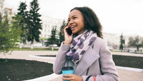 Το ελκυστικοί μικτοί smartphone ομιλίας κοριτσιών φυλών και ο καφές κατανάλωσης περπατούν στην οδό πόλεων με τις τσάντες περπατών στοκ εικόνα