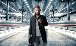Το ελκυστικό άτομο με ένα έξυπνο τηλέφωνο στο χέρι του στέκεται στην πλατφόρμα περιμένοντας το τραίνο Στοκ Εικόνα