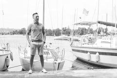 Το ελκυστικό άτομο στέκεται στη μύτη τις βάρκες στην αποβάθρα στη μαρίνα ποταμών στοκ εικόνα
