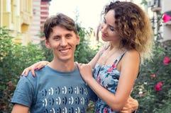 Το ελκυστικό άτομο χαμογελά, αγκαλιάζει τη φίλη του και εξετάζει τη κάμερα Το κορίτσι κτυπά ήπια το φίλο της και εξετάζει τον Αυξ στοκ εικόνες