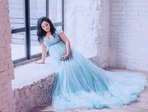 Το ελκυστικό έγκυο σκοτεινός-μαλλιαρό κορίτσι κάθεται στο μακρύ, μπλε ακριβό φόρεμα, που στηρίζεται με ένα χέρι στη στρωματοειδή  στοκ εικόνες με δικαίωμα ελεύθερης χρήσης
