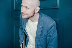 Το ελκυστικό ενήλικο επιτυχές φαλακρό γενειοφόρο άτομο στο κοστούμι με το lap-top εξετάζει τη κάμερα και χαμογελά slyly στο μπλε  στοκ εικόνες