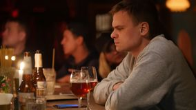 Το ελκυστικό και κουρασμένο άτομο κάθεται στο φραγμό με τη μαλακή ελαφριά μπύρα εσωτερικού φωτισμού και κατανάλωσης φιλμ μικρού μήκους