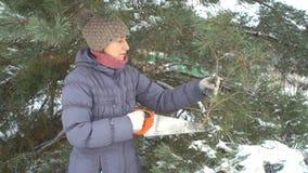 Το ελκυστικό καυκάσιο τέμνον πεύκο γυναικών διακλαδίζεται από το πριόνι στο χειμερινό χιονώδη κήπο της για τη Χαρούμενα Χριστούγε φιλμ μικρού μήκους