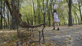 Το ελκυστικό κορίτσι εφήβων έντυσε στον κομψό ιματισμό που έχει έναν περίπατο στο πάρκο κοντά σε έναν πάγκο μια ημέρα φθινοπώρου  απόθεμα βίντεο