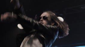 Το ελκυστικό κορίτσι με τα γυαλιά ηλίου στο μαύρο σακάκι δέρματος χορεύει ενεργά στη σκηνή απόθεμα βίντεο