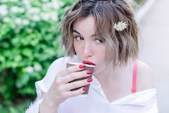 Το ελκυστικό κορίτσι με τα κόκκινα χείλια και το λουλούδι μανικιούρ whith στην τρίχα της κάθεται στο πάρκο και τον καφέ κατανάλωσ στοκ φωτογραφία