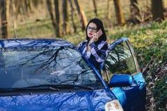 το ελκυστικό κορίτσι οδηγών κοιτάζει από τη ανοιχτή πόρτα του αυτοκινήτου και της ομιλίας Στοκ Εικόνα