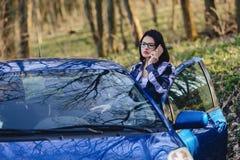 το ελκυστικό κορίτσι οδηγών κοιτάζει από τη ανοιχτή πόρτα του αυτοκινήτου και της ομιλίας Στοκ Φωτογραφίες
