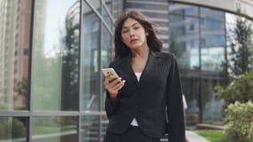 Το ελκυστικό κορίτσι σε ένα επιχειρησιακό κοστούμι χρησιμοποιεί ένα smartphone νέα επιχειρησιακή γυναίκα που ένα μήνυμα σε ένα κι απόθεμα βίντεο
