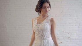 Το ελκυστικό κορίτσι σε μια ελαφριά άσπρη πολυτέλεια που το άσπρο γαμήλιο φόρεμα θέτει, στάσεις μόνο σε ένα ευρύχωρο δωμάτιο, προ απόθεμα βίντεο
