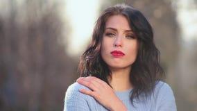 Το ελκυστικό κορίτσι brunette κινηματογραφήσεων σε πρώτο πλάνο με την όμορφη τρίχα και τα κόκκινα χείλια θέτει στη κάμερα απεικον φιλμ μικρού μήκους