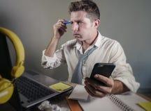 Το ελκυστικό λυπημένο και απελπισμένο άτομο χάνει μέσα τη γραβάτα εξετάζοντας ακατάστατο και πολυάσχολο το γραφείο φορητών προσωπ στοκ φωτογραφία με δικαίωμα ελεύθερης χρήσης