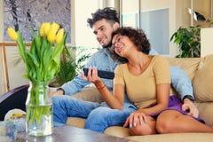 Το ελκυστικό νέο ζεύγος κάθεται σε έναν καναπέ με ένα lap-top σε έναν πίνακα σε ένα καθιστικό Στοκ φωτογραφίες με δικαίωμα ελεύθερης χρήσης