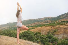 Το ελκυστικό νέο θηλυκό ασκεί τη γιόγκα στην κορυφή του υψηλού βουνού το βράδυ στοκ φωτογραφία με δικαίωμα ελεύθερης χρήσης