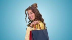 Το ελκυστικό νέο κορίτσι περιστρέφει γύρω από την τις τσάντες αγορών εκμετάλλευσης φιλμ μικρού μήκους
