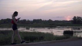 Το ελκυστικό νέο κορίτσι σχηματίζει έναν αριθμό στο τηλέφωνο στο υπόβαθρο ενός μόνου κοριτσιού ηλιοβασιλέματος που περπατά κοντά  απόθεμα βίντεο