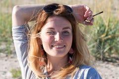 Το ελκυστικό νέο ξανθό κορίτσι έριξε το χέρι της με ένα μολύβι πίσω Στοκ Εικόνα