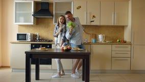 Το ελκυστικό νέο χαρούμενο ζεύγος έχει τη διασκέδαση που χορεύει και που τραγουδά μαγειρεύοντας στην κουζίνα στο σπίτι στοκ φωτογραφία