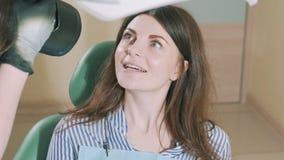 Το ελκυστικό σκοτεινός-μαλλιαρό νέο κορίτσι σε ένα γραφείο γιατρών ` s κάθεται σε μια οδοντική καρέκλα, θεραπευμένα δόντια, ένας  απόθεμα βίντεο