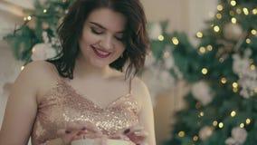 Το ελκυστικό χαμόγελο γυναικών κοντά στο χριστουγεννιάτικο δέντρο και ανοίγει παρουσιάζει φιλμ μικρού μήκους