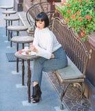 Το ελκυστικό brunette γυναικών τρώει το γαστρονομικό υπόβαθρο πεζουλιών καφέδων κέικ Γαστρονομική απόλαυση Το κορίτσι χαλαρώνει τ στοκ εικόνα