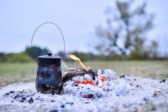 Το εμπορευματοκιβώτιο στους άνθρακες για να κάνει το τσάι κατά τη διάρκεια του ταξιδιού στοκ φωτογραφία