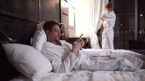 Το ενήλικο άτομο βάζει κρεβατιών στο κινητό τηλέφωνο στο άνετο ξενοδοχείο απόθεμα βίντεο