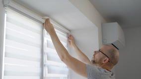 Το ενήλικο άτομο εγκαθιστά μια ράβδο για τους τυφλούς σε ένα πλαίσιο παραθύρων σε ένα καθιστικό στις πρωινές και κουρτίνες καθορι απόθεμα βίντεο