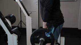 Το ενήλικο άτομο με το υπερβολικό βάρος αποδίδει deadlift στη γυμναστική φιλμ μικρού μήκους