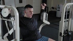 Το ενήλικο άτομο με το υπερβολικό βάρος εκπαιδεύει το στήθος του στον προσομοιωτή φιλμ μικρού μήκους