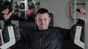 Το ενήλικο άτομο με το υπερβολικό βάρος εκπαιδεύει το στήθος του στον προσομοιωτή απόθεμα βίντεο