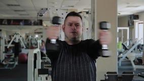Το ενήλικο άτομο με το υπερβολικό βάρος εκτελεί την αναπαραγωγή με τους αλτήρες φιλμ μικρού μήκους