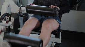 Το ενήλικο άτομο με το υπερβολικό βάρος εκτελεί την επέκταση ποδιών απόθεμα βίντεο