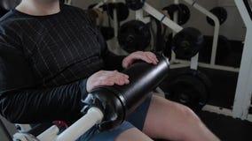 Το ενήλικο άτομο με το υπερβολικό βάρος εκτελεί την επέκταση ποδιών φιλμ μικρού μήκους