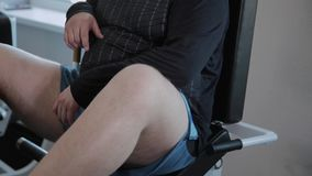 Το ενήλικο άτομο με το υπερβολικό βάρος πιέζει τα πόδια του στον προσομοιωτή απόθεμα βίντεο