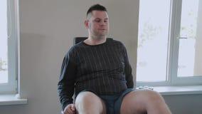 Το ενήλικο άτομο με το υπερβολικό βάρος πιέζει τα πόδια του στον προσομοιωτή φιλμ μικρού μήκους