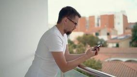 Το ενήλικο γενειοφόρο άτομο διαβάζει τα μηνύματα τηλεφωνικώς που κλίνουν στα κιγκλιδώματα του μπαλκονιού απόθεμα βίντεο