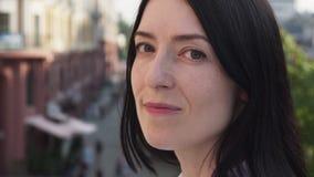 Το ενήλικο κεφάλι στροφών γυναικών brunette και εξετάζει τη κάμερα στην πόλη απόθεμα βίντεο