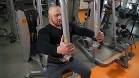 Το ενήλικο bodybuilder κάθεται στον προσομοιωτή και διαδίδει τα όπλα του γύρω, που ανυψώνουν πολύ βάρος 4K η αργή Mo απόθεμα βίντεο