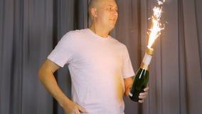 Το ενήλικο caicasian άτομο ανάβει μια πηγή πυρκαγιάς σε ένα μπουκάλι της σαμπάνιας Η πυρκαγιά πυροτεχνημάτων συμβολίζει μια εορτα φιλμ μικρού μήκους