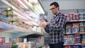 Το ενήλικο άτομο επιλέγει τις παιδικές τροφές στα ράφια στην υπεραγορά φιλμ μικρού μήκους
