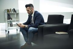 Το ενήλικο άτομο σε ένα σακάκι και τα γυαλιά που λογαριάζουν χρησιμοποιώντας το τηλέφωνο σύνδεσε με το δίκτυο σερφ wifi Στοκ Εικόνες