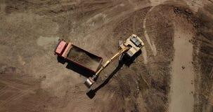 Το εναέριο μήκος σε πόδηα του εκσκαφέα χύνει την άμμο στο φορτηγό απόθεμα βίντεο