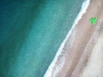 Το εναέριο νερό turquois άποψης της ιόνιας θάλασσας στην Αλβανία, πέτρες στην ακτή και το γίγαντα διόγκωσε τη τοπ άποψη κάκτων στοκ φωτογραφία