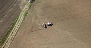 Το εναέριο πανοραμικό βίντεο από τον κηφήνα των γεωργικών τομέων, τρακτέρ με το άροτρο οργώνει το έδαφος για τη σπορά των συγκομι απόθεμα βίντεο