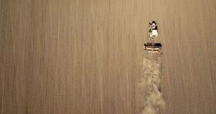 Το εναέριο πανοραμικό βίντεο από τον κηφήνα των γεωργικών τομέων, τρακτέρ με το άροτρο οργώνει το έδαφος για τη σπορά των συγκομι φιλμ μικρού μήκους