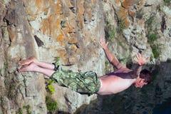 Το ενεργό άτομο βουτά από έναν απότομο βράχο Στοκ Φωτογραφίες